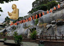 Buddhist temple Dambulla Sri Lanka. Famous buddhist temple Dambulla Sri Lanka with big golden Buddha on the roof and a row sculptures of monks in orange sari Royalty Free Stock Photos