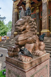 The Buddhist temple Datsan Gunzechoinei. The chinese guardian lion Foo Dog near the entrance. Stock Images