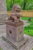 The Buddhist temple Datsan Gunzechoinei. The chinese guardian lion Foo Dog near the entrance. Stock Photos