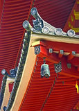Buddhist temple details. A closeup of the highly decorated flying eaves and red roofs of the Japanese Byodo-in temple in Oahu, Hawaii Royalty Free Stock Photography