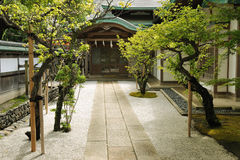 Buddhist temple entrance. Scenic way among green trees to the Japanese temple entrance Stock Photography