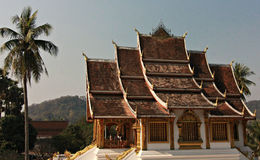 Buddhist Temple in Luang Prabang, Laos. Palm tree and Buddhist temple sits in Luang Prabang with tall hills in the background Royalty Free Stock Photo
