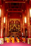 Buddhist Temple and Monks. A small group of Buddhist monks sit down in prayer in front of a statue of buddha in an elaborately decorated temple Stock Photos