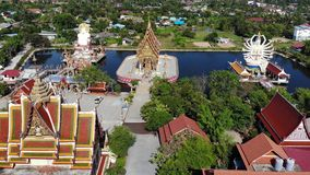 Buddhist temple near lake. Drone top view of roofs and statues of wonderful Buddhist temple located near lake on sunny. Day on Ko Samui. Wat Plai Laem with stock footage