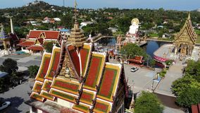 Buddhist temple near lake. Drone top view of roofs and statues of wonderful Buddhist temple located near lake on sunny. Day on Ko Samui. Wat Plai Laem with stock video