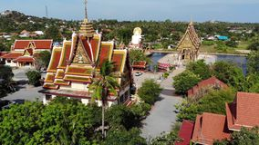 Buddhist temple near lake. Drone top view of roofs and statues of wonderful Buddhist temple located near lake on sunny. Day on Ko Samui. Wat Plai Laem with stock video footage