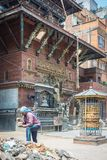 Buddhist temple in Nepal with worker moving rubble stock image
