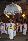 A Buddhist temple priest walks through the streets of Kandy during the Esala Perahera in Sri Lanka. Stock Image
