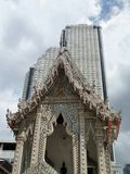 Buddhist temple and tall condominium building in Bangkok Royalty Free Stock Photo