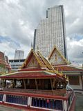 Buddhist temple and tall condominium building in Bangkok Royalty Free Stock Photography