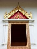 Buddhist temple window with Thai painting design. Stock Photos