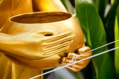 Hands of the Buddha holding an alms bowl. Royalty Free Stock Photography