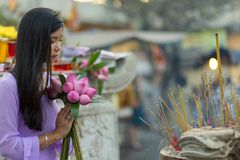 Buddhist woman praying at temple Stock Photo