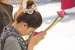 Buddhist woman praying. A young woman with a pink cell phone praying to Buddha in Thailand Royalty Free Stock Photos