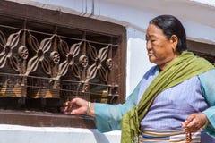 Buddhist Woman Turning Prayer Wheels Stock Photo