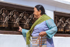 Buddhist Woman Turning Prayer Wheels stock image