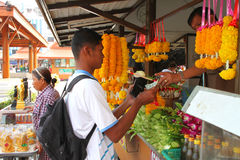 Buddhist worship and making religious merit. KORAT, THAILAND - JANUARY 16 : The unidentified Buddhist is selling flowers and oblations to worship sacred item and royalty free stock image