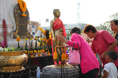 Buddhist worshiping and making religious merit. KORAT, THAILAND - JANUARY 16 : The unidentified Buddhists are worshiping Thao Suranari statue and making royalty free stock photo