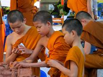 Buddhist young monks doing hand crafts in the temple yard. A bhikkhu, an ordained male monastic. Buddhist monk Pali, Sanskrit bhiksu. Young Buddhist monks royalty free stock photos