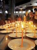 Buddhisten, die Kerzen beleuchten Stockfoto