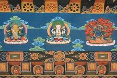 Buddhistische Göttlichkeiten und verschiedene Muster werden gemalt auf einer Wand eines Tempels (Bhutan) Lizenzfreie Stockfotos