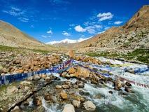 Buddhistische Gebetsflaggen über dem kleinen Fluss mit blauem Himmel und Berg auf Hintergrund Stockfotografie