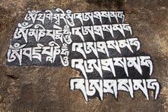 Buddhistische Gebetssymbole auf Stein stockfotografie