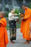 Buddhistische Mönche, die Almosen montieren stockfotografie