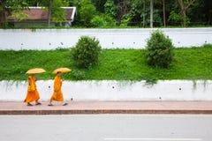 Buddhistische Mönche, die auf die Straße von Luang Prabang, Laos gehen Stockfoto