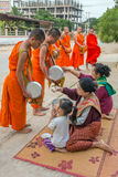 Buddhistische Mönche, die morgens Almosen in Vang Vieng, Laos sammeln Stockbilder