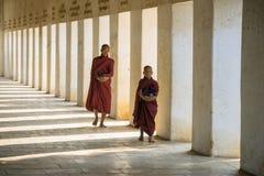 Buddhistische Mönche, die an Shwezigon-Tempel gehen Stockfotografie