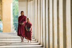 Buddhistische Mönche, die an Shwezigon-Tempel gehen Stockfotos