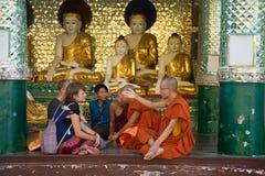 Buddhistische Mönche verständigen sich mit den europäischen Touristen in einem der Tempel der Shwedagon-Pagode Yangon, Myanmar Lizenzfreies Stockfoto