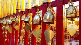 Buddhistische Messingglocke, die am roten Zaun hängt Stockbild