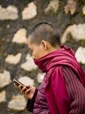 Buddhistische Nonne, die mit ihrem Handy texting ist Lizenzfreie Stockbilder