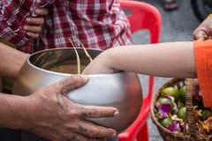 Buddhistischen Mönchen werden das Lebensmittel gegeben, das von den Leuten anbietet Lizenzfreie Stockfotos