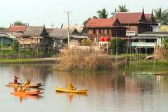 Buddhistischen Mönchen werden das Lebensmittel gegeben, das von den Leuten durch Boot anbietet Stockfoto