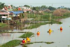 Buddhistischen Mönchen werden das Lebensmittel gegeben, das von den Leuten durch Boot anbietet Stockfotos