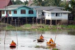 Buddhistischen Mönchen werden das Lebensmittel gegeben, das von den Leuten durch Boot anbietet Lizenzfreie Stockfotografie