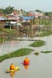 Buddhistischen Mönchen werden das Lebensmittel gegeben, das von den Leuten durch Boot anbietet Stockbild