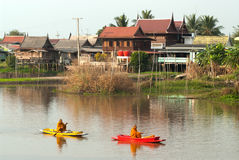Buddhistischen Mönchen werden das Lebensmittel gegeben, das von den Leuten durch Boot anbietet Stockfotografie