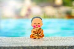 Buddhistischer Junge im Urlaub, der im glücklichen Sommer des Lotussitzes am Rand des Pools sitzt Mitte, Nahaufnahme stockbild