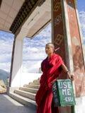 Buddhistischer Mönch in Buthan, das auf einem Abfallstauraum sich lehnt Stockfoto