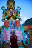 Buddhistischer Mönch, der zu enormer Buddha-Statue betet Lizenzfreie Stockfotografie