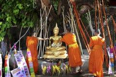 Buddhistischer Mönch, der zur Buddha-Statue gießt Lizenzfreie Stockfotos