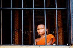 buddhistischer Mönch des jungen Anfängers, der das Schauen außerhalb des Fensters von seinem Kloster späht stockbild