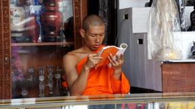 Buddhistischer Mönch liest ein Buch innerhalb eines Systems Lizenzfreies Stockbild