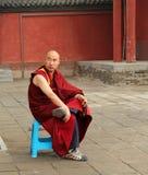 Buddhistischer Mönch mit dem Rosenbeet, das im Yard von Dazhao-Kloster sitzt Stockbilder