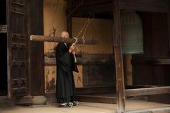 Buddhistischer Mönch schellt eine Glocke Stockbild