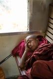 Buddhistischer Mönch schläft auf hölzernem Zugsitz stockbilder